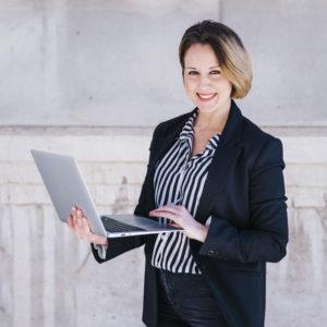donna-di-affari-che-passa-in-rassegna-il-computer-portatile-sulla-via_23-2147787729
